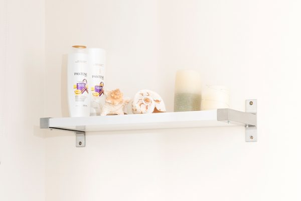 Flexi Storage Decorative Shelving Style Shelf White Gloss 600 x 190 x 24mm fitted on wall with decorations on top