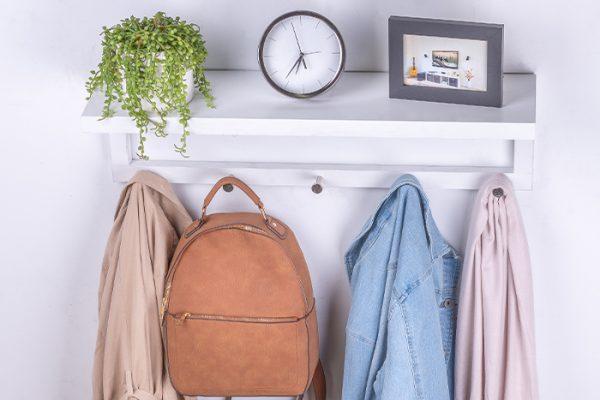 Flexi Storage Decorative Shelving Coat Shelf With Hooks White installed on wall with decorations on shlef and coats and bag hanging on hooks
